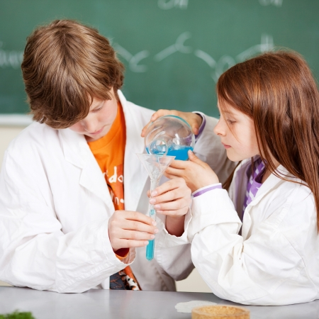 Young boy and girl in school learning chemistry working together as a team pouring liquids through a funnel into a test tube photo