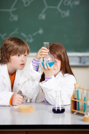 fascinating: A fascinating experiment captures the attention of two young students in a chemistry class at school Stock Photo