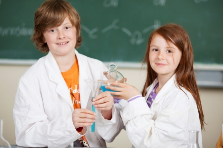 Young girl and boy doing chemistry dressed in labcoats holding glass flasks filled with a turquoise mixture photo