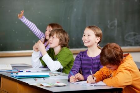 Sourire amical petite fille en classe regardant l'avant de la classe tandis que l'un de ses amis agite sa main en l'air pour répondre à une question