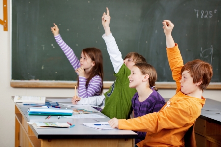 Clever young students in class holding their hands in the air in response to a question as they vie to give the answer photo