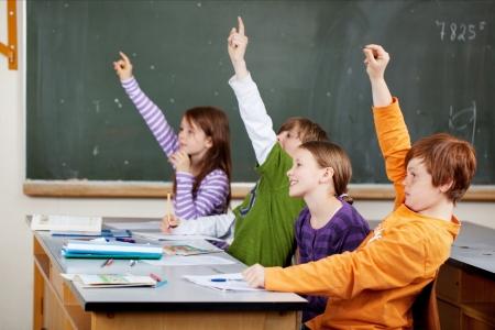 Jóvenes estudiantes inteligentes de la clase que sostienen sus manos en el aire en respuesta a una pregunta, ya que compiten para dar la respuesta