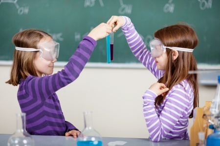 science lesson: Two little students doing biochemistry research at the classroom