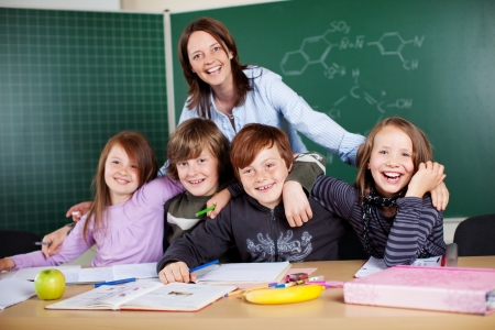 schooling: Portrait of happy teacher and her students inside the classroom Stock Photo
