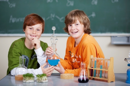 Two young students in chemistry class sitting at a desk surrounded by scientific glassware and colourful mixtures photo
