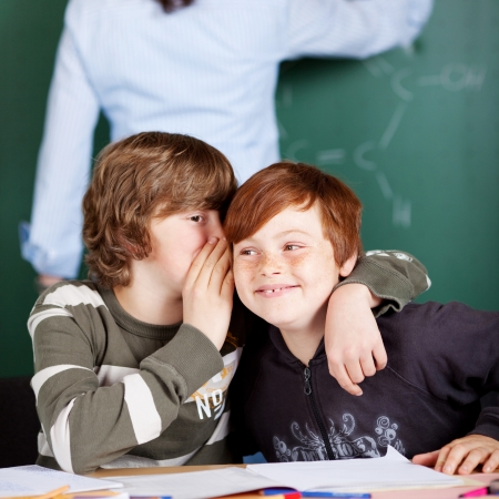 Two young boys sharing secrets sitting in the classroom with their heads close together whispering photo
