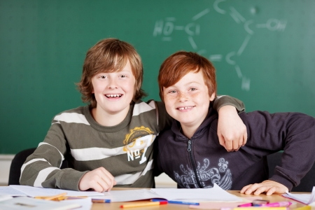 arms around: Portrait of two happy students sitting inside the classroom Stock Photo