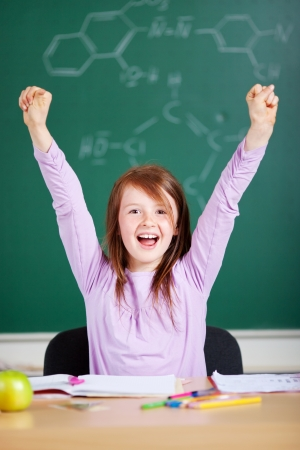 people sitting on chair: Jubilant excited little girl in school cheering and raising her arms in the air against a blackboard background Stock Photo