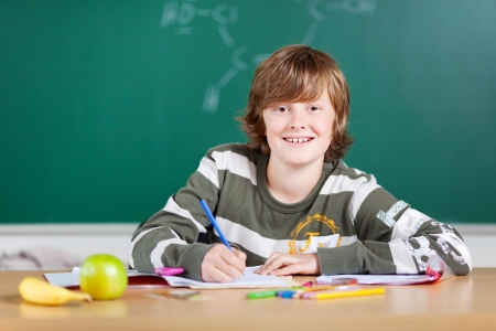 kids writing: Smiling student writing on his note inside the classroom
