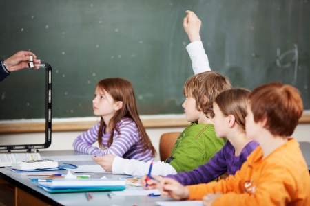 put up: Diligent student raising his hand in a school class