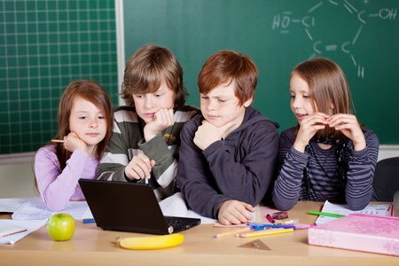 netbook: Group of young schoolchildren sitting at a desk in the classroom looking at a laptop in puzzlement