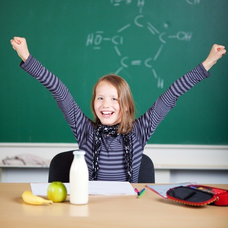 jubilate: Happy student raising her hand inside the classroom