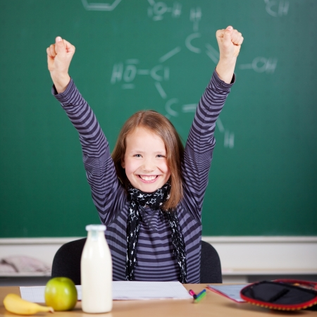 jubilate: Smiling student raising her hands at the classroom