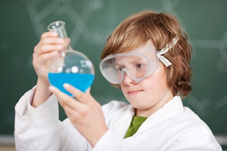 Young boy performing chemistry experiments at the lab photo