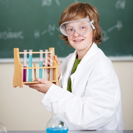 Smiling young student in chemistry class wearing safety goggles and holding up a rack of test tubes photo