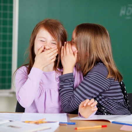 kids class: Laughing little girls sharing secrets in class sitting in front of the blackboard whispering to each other