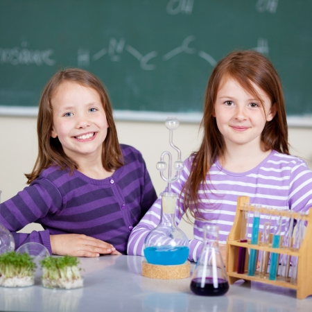 Smiling young students with liquid formula and cress at the classroom