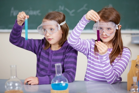 Two female students at the table with chemical reagents and holds test tube in his hands Stock Photo