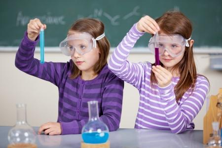 Zwei Studentinnen am Tisch mit chemischen Reagenzien und hält Reagenzglas in der Hand