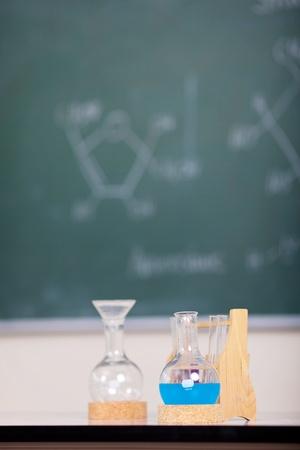 Laboratory glassware and liquid formula in chemistry class photo