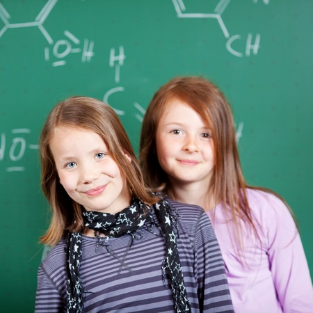 formulae: Two pretty little girls in school standing close together in front of a blackboard covered in atomic formulae