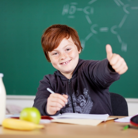 mid teens: Happy little boy giving a thumbs up gesture of success while seated working at his desk in the schoolroom with a blackboard background