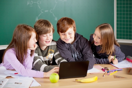 mid teens: Schoolchildren working with laptop at the classroom Stock Photo