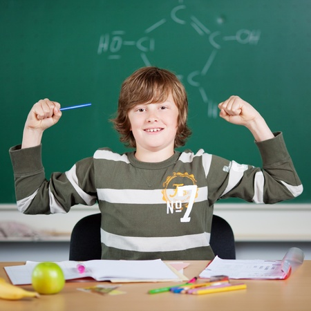 boy muscles: Portrait of young strong pupils at the classroom