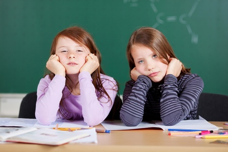 tiresome: Portrait of bored students sitting at the classroom