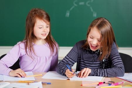 Dvě mladé dívky, pracující svou lekci ve třídě Reklamní fotografie - 21279471