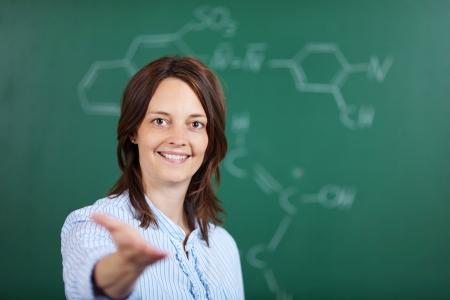 invitando: Retrato de la sonrisa profesor mostrando algo en el interior del salón de clases