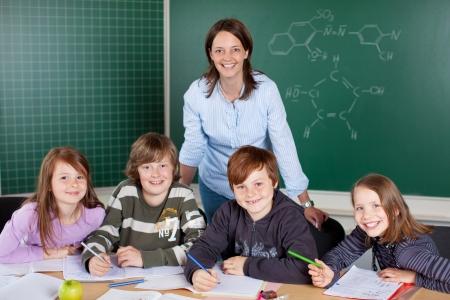 Šťastný třída mladých žáků s jejich mladá žena učitel pracující společně ve třídě sdílení stůl Reklamní fotografie - 21344713