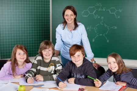 Happy class of young pupils with their young female teacher working together in a classroom sharing a desk Reklamní fotografie - 21344713