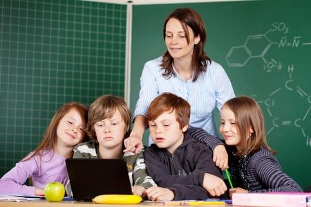 Portrét žáků se dívá na notebooku při poslechu učitele vysvětlovat něco, Reklamní fotografie - 21279514