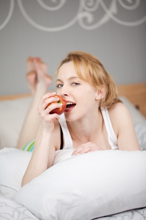 Portrait of young woman eating apple while lying on bed photo
