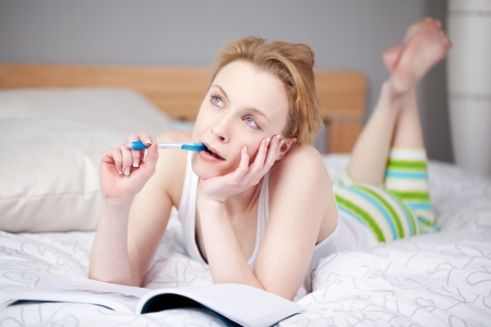 pyjama: Thoughtful young woman with book and pen looking away while lying in bed