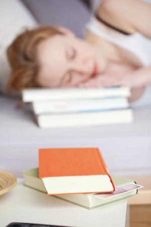 night table: Portrait of blurred sleeping woman with book