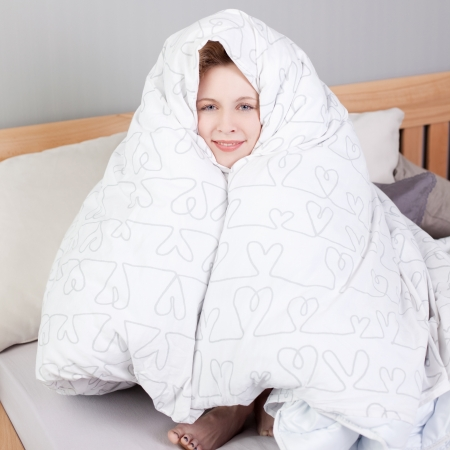 warm house: Portrait of young woman wrapped in blanket while sitting in bed