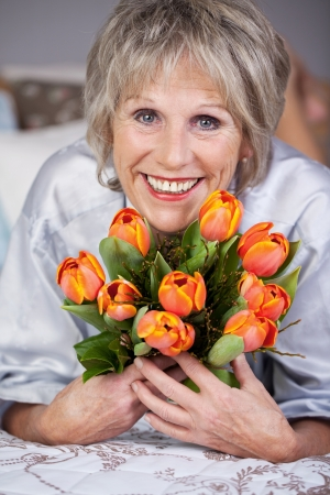 woman short hair: Portrait of senior woman holding bunch of tulips in bed Stock Photo