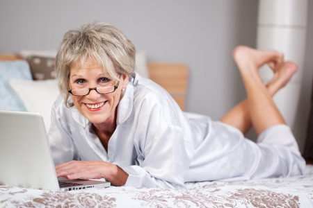 savvy: Happy senior woman lying on bed and browsing through laptop