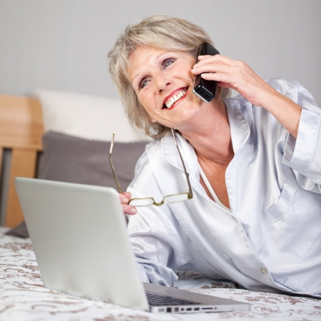 costumer: Happy senior woman with laptop using cordless phone while lying in bed Stock Photo
