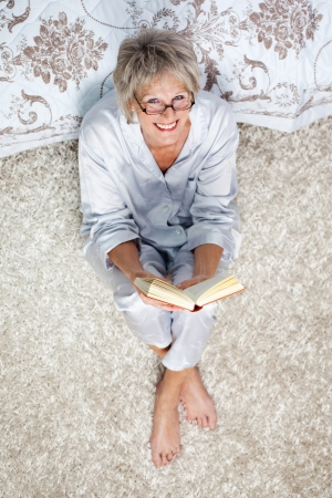 reading glasses: High angle portrait of senior woman holding book while sitting on rug in bedroom Stock Photo