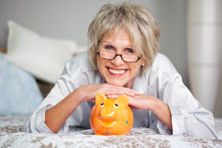pensioner: Conceptual portrait of happy senior female lying on bed with piggybank