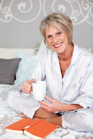 Smiling senior woman sitting on bed with book while drinking coffee photo