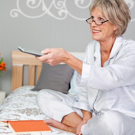 changing channels: Happy senior woman using remote control to changing channels while sitting on bed
