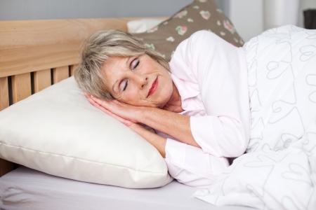 Senior vrouw die lacht tijdens het slapen in bed Stockfoto