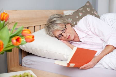 recuperating: Concentrated senior woman reading book while lying in bed