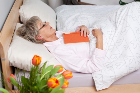recuperating: Senior woman fall asleep while reading a book in bed