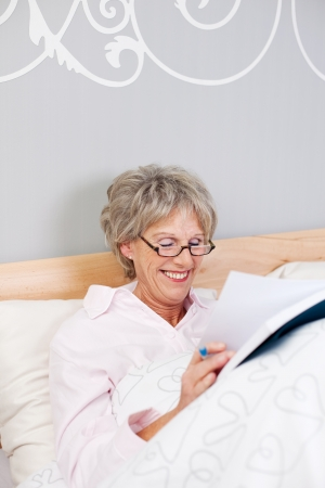 Happy senior woman wearing glasses while reading book in bed photo