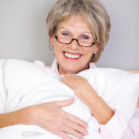 Happy senior woman wearing glasses embracing pillow photo